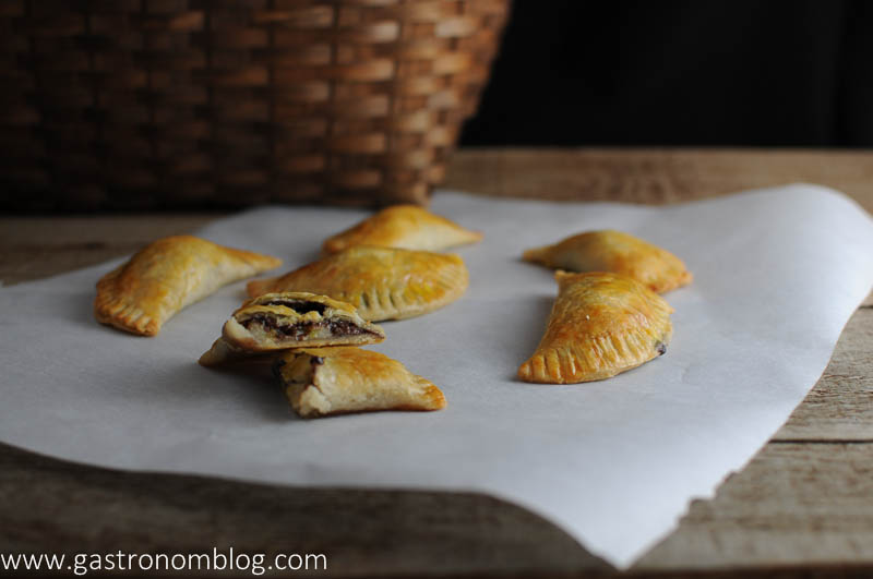 Banana and Nutella Hand pies on parchment paper. Basket in background.